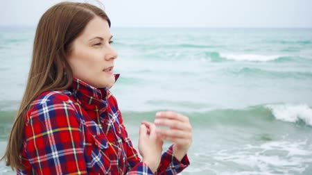 see off : Young woman looking at big sea waves on beach. Female traveler is cold during vacation on beach at stormy weather while off-season. Breeze from ocean blowing her hair in slow motion