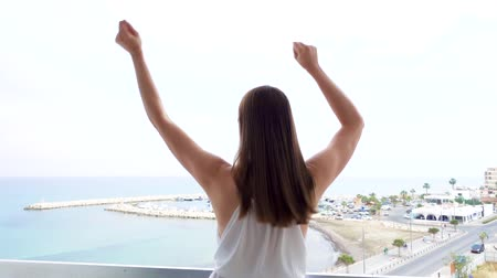 рука : Funny young woman in white dress jumping with joy on terrace with sea view. Silly female raising arms up and dancing. Happy overjoyed girl having fun in slow motion Стоковые видеозаписи