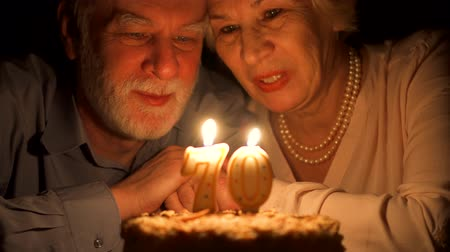 romance : Loving senior couple celebrating anniversary with cake at home in evening. Happy elderly family hugging, cuddling together, make wishes and blowing out candles in form of number 70. Focus on seniors