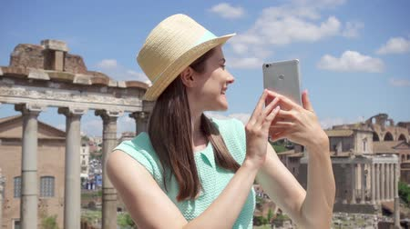 wanderlust : Woman near ancient ruins Forum Romanum using mobile phone in slow motion. Female tourist having video chat via online app against Roman forum in center of Rome, Italy. Student travel through Europe Stock Footage
