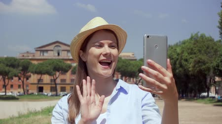 circus : Young woman walking on Circus Maximus and using mobile phone in slow motion in Rome, Italy. Happy female traveler enjoying vacation in european city. Smiling girl having video chat via online app Stock Footage