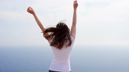 uzanmış : Young woman in white t-shirt jumping with joy at cliff against blue sea on sunny day. Carefree overjoyed female traveler dancing against breathtaking view of blue Mediterranean sea