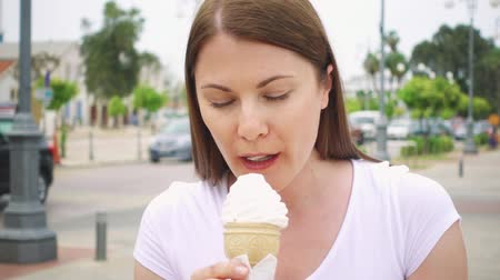 kypr : Young woman in white t-shirt enjoying soft vanilla ice cream in waffle cone outdoors in slow motion. Female traveler eating natural healthy frozen yogurt on street alone