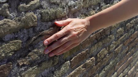 press wall : Woman sliding hand against old ancient red brick wall in slow motion. Female hand touching hard rough surface of stone bridge