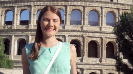 colosseo : Young woman standing on background of famous Roman attraction Colosseum in Rome, Italy in slow motion. Happy female tourist enjoying her european summer vacation. Student travel through Europe