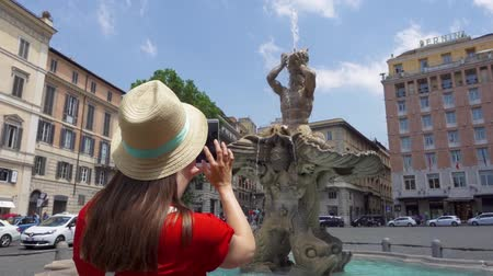 triton : ROME, ITALY - CIRCA May 2018: Woman in hat on Barberini square in Rome, Italy taking photo on mobile phone in slow motion. Happy female tourist taking picture of famous Triton Fountain. Student travel