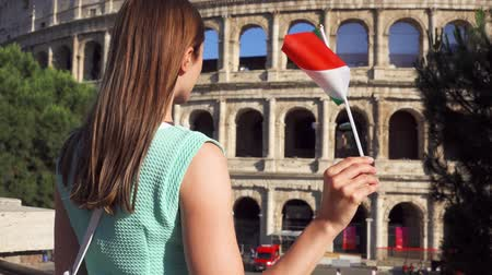 colosseo : Young woman standing near famous attraction Colosseum in Rome, Italy. Teenage girl waving Italian flag in slow motion. Happy female tourist enjoying european vacation. Student travel through Europe