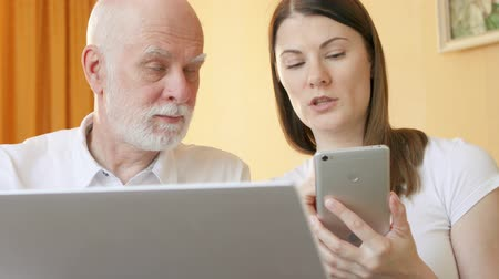 use laptop : Senior father and his young daughter using cellphone at home. Teen granddaughter teaching grandfather computer literacy, explaining how smartphone works. Active modern life after retirement. Stock Footage