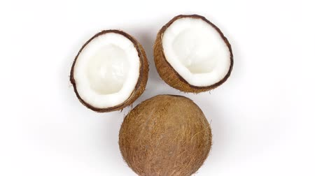 rehydration : Top view of one whole ripe brown tropical coconut and two halves with yummy white pulp rotating on white isolated background. Healthy fresh tropical fruits. Loopable seamless cocos rotating