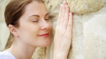 press wall : Woman sliding hand against old stone wall in slow motion. Female face pressed against wall while hand touching hard rough surface of rock on sunny summer day. Focus on hand. Shallow depth of field
