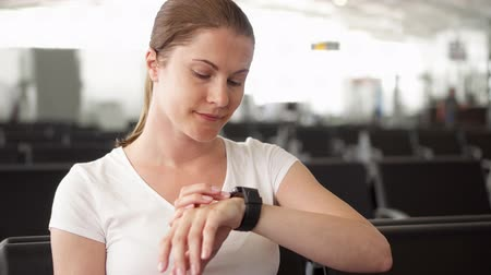 časová prodleva : Young woman in white t-shirt sitting in airport waiting room. Female traveler checking time on smart watch while waiting for flight departure Dostupné videozáznamy
