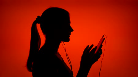 contornos : Silhouette of young woman listening to music on smart phone. Females face in profile putting on ear-phones on red background. Black contour shadow of teenagers half-face singing and dancing