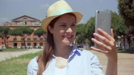 viajante : Young woman walking on Circus Maximus and using mobile phone in slow motion in Rome, Italy. Happy female traveler enjoying vacation in european city. Smiling girl having video chat via online app Stock Footage