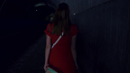 dread : Back view of young woman in red dress walking alone in tunnel at night. Scared female running fast from her pursuer at night. Girl turning around to see who is behind. Concept of crime and violence Stock Footage