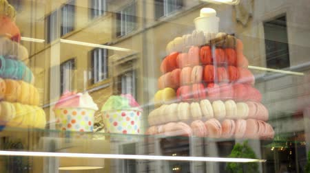 candy : Colorful fresh macarons behind glass showcase. Street and house reflections in storefront with sweet french cookies. Beautiful bakery shop-window decoration