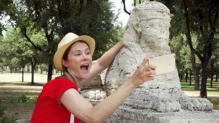 esfinge : Woman in red dress and hat doing silly selfie with sphinx statue on mobile phone in slow motion. Happy female tourist taking funny picture in Villa Borghese. Student travel through Europe