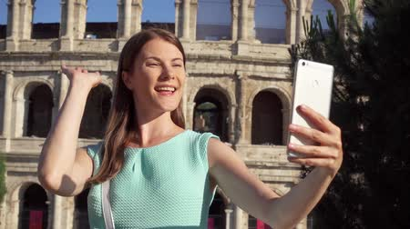 colosseo : Woman do selfie on mobile phone near famous attraction Colosseum in Rome, Italy. Teenage girl smiling in slow motion. Happy female tourist enjoying her european vacation. Student travel through Europe Stock Footage