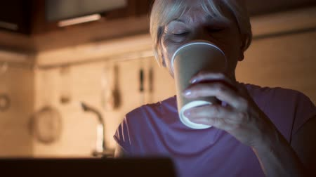Sleepy senior woman sit in kitchen use laptop at home-office. Tired female pensioner drink coffee from paper cup while work on computer at night. Overworked businesswoman work on project in evening