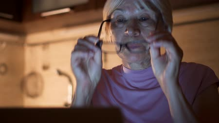Senior woman with glasses at home work on laptop from home-office at night. Overworked exhausted businesswoman take off spectacles and rub her tired eyes in kitchen in evening