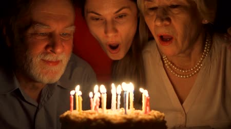 Loving senior couple ann their daughter celebrating with cake at home in the evening. Happy family hugging, cuddling together, make wishes and blowing out candles in slow motion. Focus on people