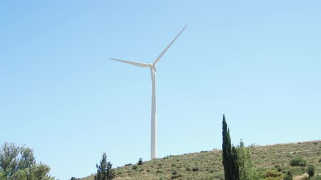 Green hill with windmills in Larnaca, Cyprus. Wind power technology - wind turbine against blue sky. Clean and renewable energy resource of alternative energy production Stock mozgókép
