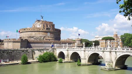 View of medieval St. Angelo castle from the other side of Tiber river. Castello SantAngelo fortress and bridge on sunny day in Rome, Italy in slow motion Stock mozgókép