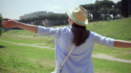 Slow motion of young woman raising arms up and dancing at Circus Maximus in Rome, Italy. Carefree female traveler enjoying vacation in european city. Happy girl spining and whirling around herself Stok Video