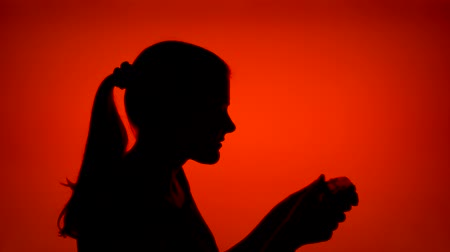 Silhouette of young woman gamer playing video game online. Females face in profile with game console on red background. Black contour shadow of teenagers half-face winning computer game