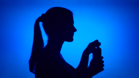 Silhouette of young woman opening can of soft drink on red background. Females face in profile drinking soda from tin. Black contur shadow of teenagers half-face