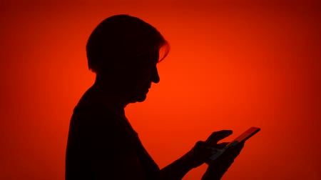 Silhouette of senior woman using mobile on red background. Females black contur of face in profile receiving good news on cellphone excited. Concept of success and being winner
