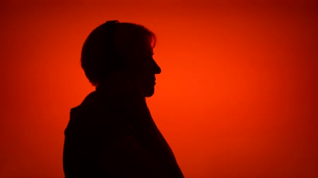 Silhouette of senior woman putting on big black wireless headphones on red background. Females face in profile listening to music. Black contur shadow of grandmothers half-face singing