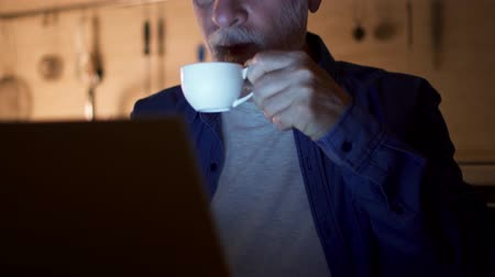 Senior man drink coffee from cup while read news on laptop. Freelancer use computer at night work from home office. Overworked businessman work on project in kitchen in evening. Camera moving up