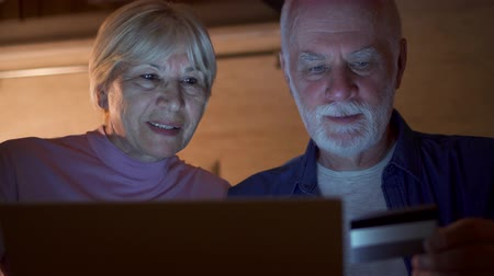 Senior couple sitting at home in kitchen at night. Retired family shopping online with credit card on laptop. Concept of technology use by older people. Active modern life after retirement