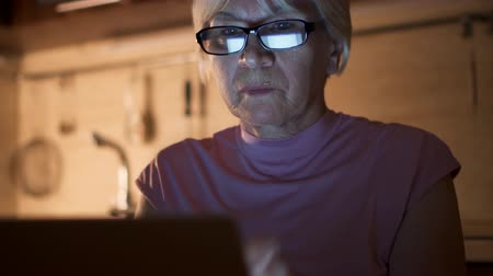 Senior woman with glasses at home read news on laptop. Freelancer use computer at night work hard from home-office. Overworked businesswoman put on spectacles in kitchen in evening. Camera moving up