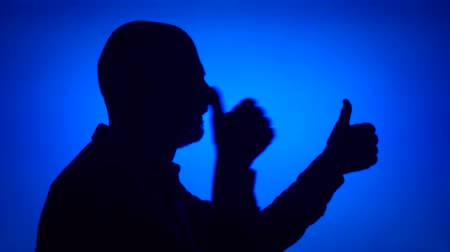 Silhouette of silly senior man having fun making thumb up gestures on blue background. Males face in profile showing thumbs-up signs. Black contur shadow of grandfathers half-face laughing
