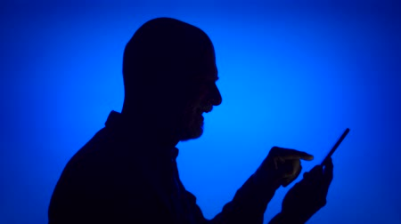 Silhouette of senior man using mobile on blue background. Males black contur of face in profile receiving good news on cellphone excited. Concept of success and being winner