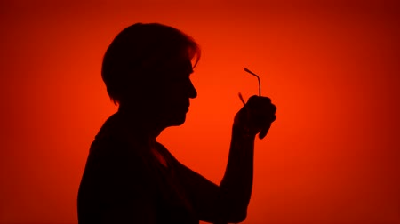 Silhouette of senior woman with eyeglasses. Females face in profile putting on glasses on red background. Black contour shadow of grandmothers half-face holding spectacles