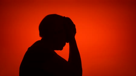 melankoli : Silhouette of senior frustrated woman. Females face in profile in despair on red background. Black contour shadow of sad grandmothers half-face showing strong negative emotions