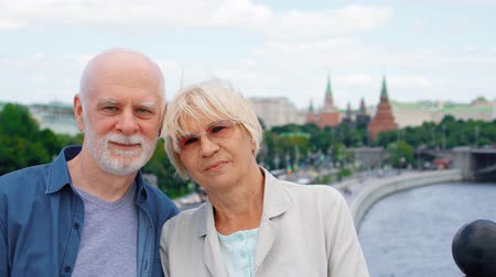 Portrait of happy senior couple standing on observation deck looking at camera. Pensioners traveling in Russia. Moscow city landscape and river on background. Hand-held camera Stok Video