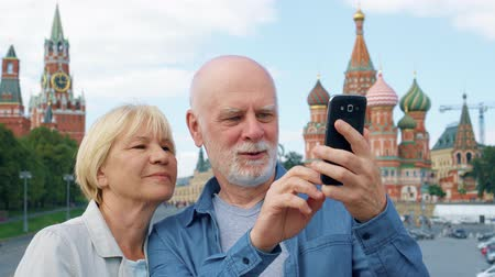Snior couple on Basils Descent take pictures on mobile phone. Traveling pensioners take photo in Moscow, Russia. Red Square, St. Basils Cathedral and Kremlin clock on background. Hand-held camera