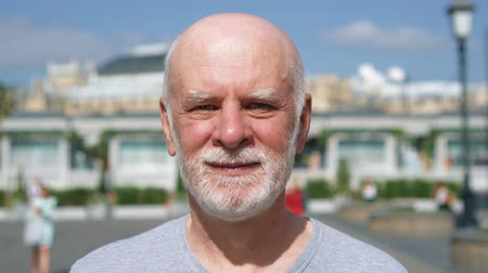 Portrait of smiling man standing outdoors looking at camera. Male pensioner traveling in Moscow, Russia. People walking around. Hand-held camera