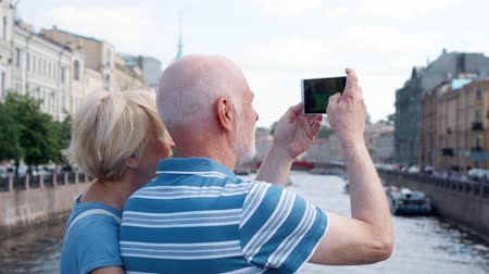 Back view of senior couple standing on embankment of canal taking pictures on mobile phone. Happy loving pensioners travel in Saint Petersburg, Russia and take photo. Hand-held camera