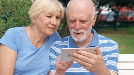 bank : Senior couple having great time sitting on bench in park chatting relaxing, browsing in smartphone. Happy family enjoying summer vacation outdoors. Hand-held camera Stok Video