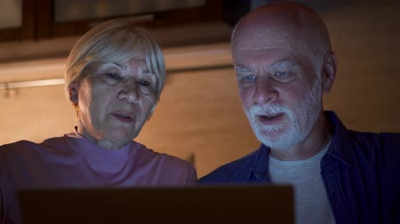 Senior couple at home using laptop in kitchen at night. Retired family working on computer learning social media. Computer literacy among elderly people, active modern lifestyle on retirement Stock mozgókép