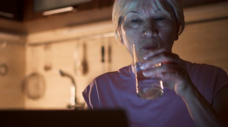 Senior woman drink water from glass while read news on laptop. Female freelancer use computer at night work from home office. Overworked businesswoman work on project in kitchen in evening