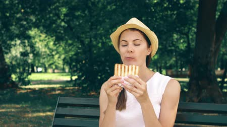 famished : Hungry young woman in white shirt sitting on bench and eating grilled sandwich with ham in public park. Tourist in hat having lunch in garden enjoying summer sunny day. Green trees on background