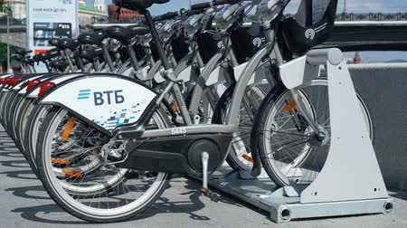 строк : MOSCOW, RUSSIA- CIRCA August 2018: VTB bicycle parking in Moscow. Gray city bikes parked on street. Hand-held camera
