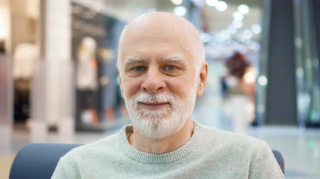 Portrait of senior man sitting in mall looking at camera. Male shopper in shopping center, smiling. Shop-windows with dummys and moving escalator on background. Hand-held camera
