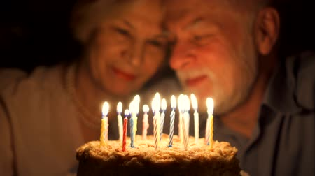 Loving senior couple celebrating anniversary with cake at home in the evening. Happy elderly family hugging, cuddling together, make wishes and blowing out candles. Focus on the cake