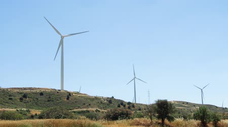 Green hill with windmills in Larnaca, Cyprus. Wind power technology - wind turbine against blue sky. Clean and renewable energy resource of alternative energy production Stok Video